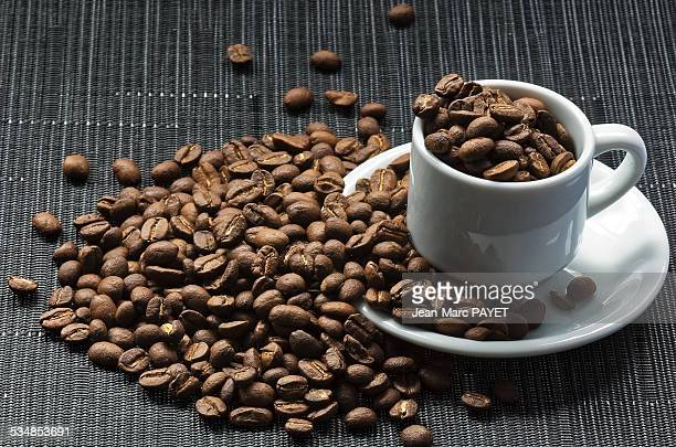 coffee cup filled with coffee beans - jean marc payet stock pictures, royalty-free photos & images