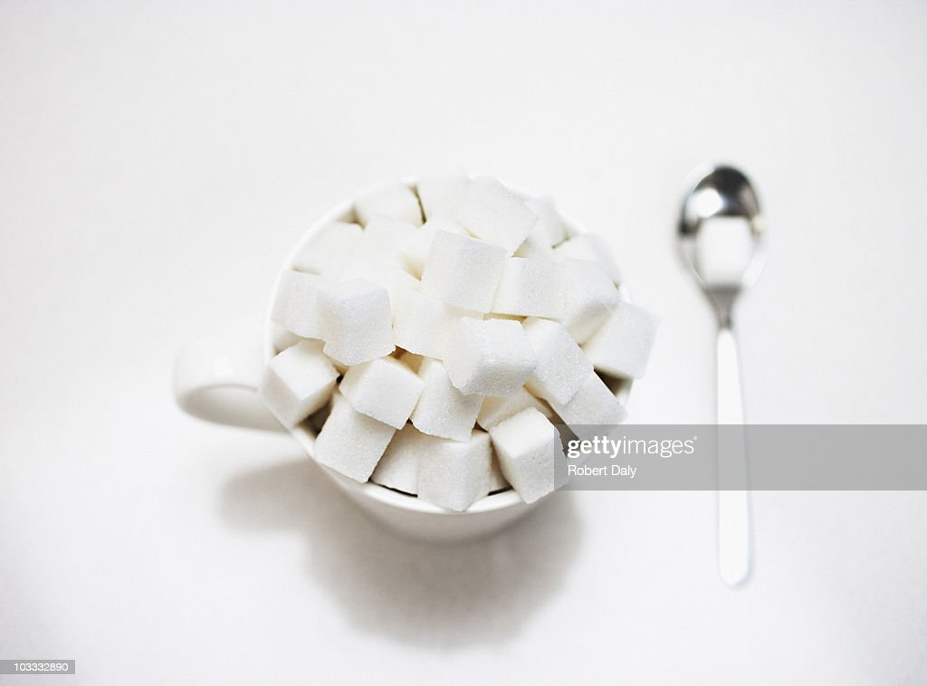 Coffee cup filled with sugar cubes : Stock Photo