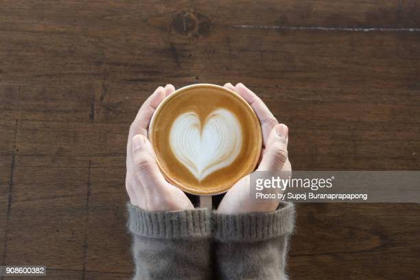 coffee cup in coffee shop.female hands holding cup of coffee on wooden table background - cafe imagens e fotografias de stock