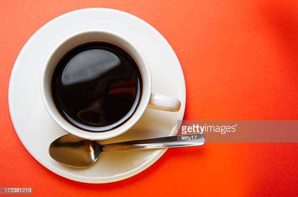 A coffee cup on a plate set against an orange background