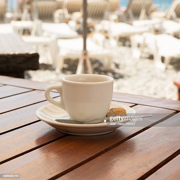 coffee cup on a wooden table front the sea - jean marc payet stockfoto's en -beelden
