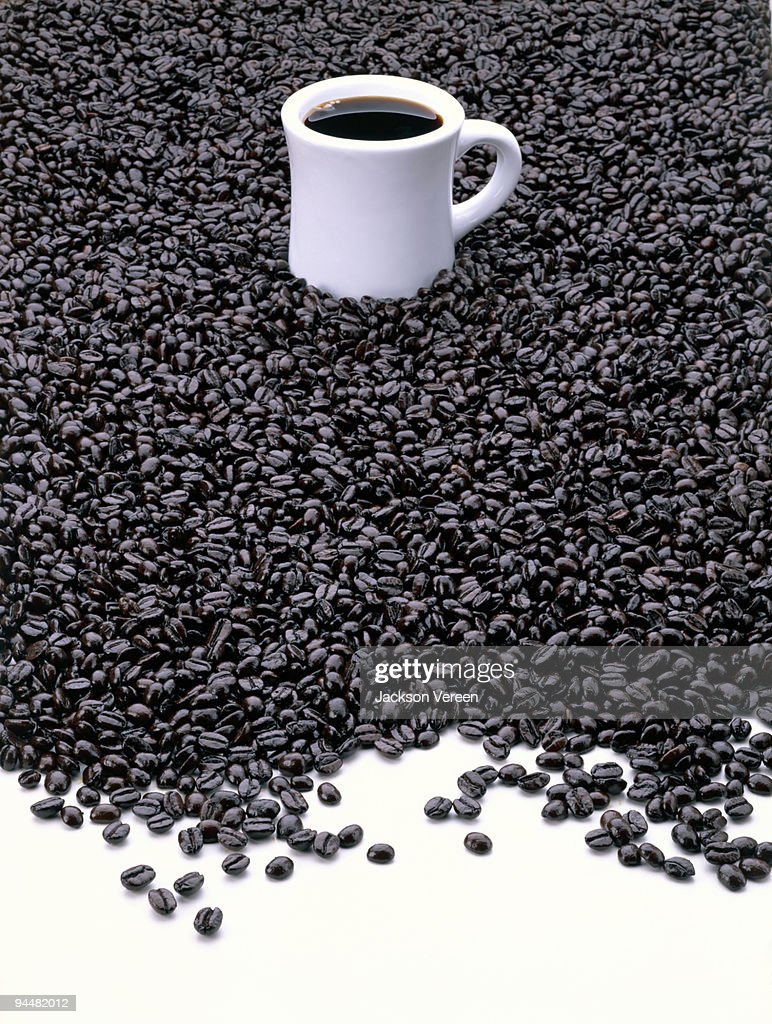 Coffee cup on pile of coffee beans : Stock Photo