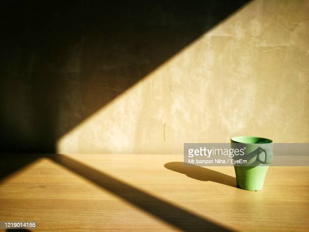 coffee cup on table against wall - ombra in primo piano foto e immagini stock