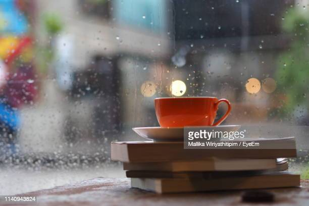 Coffee Cup On Table By Window During Rainy Season