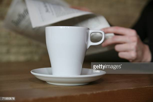Coffee cup on table in cafe with woman sitting in background reading newspaper