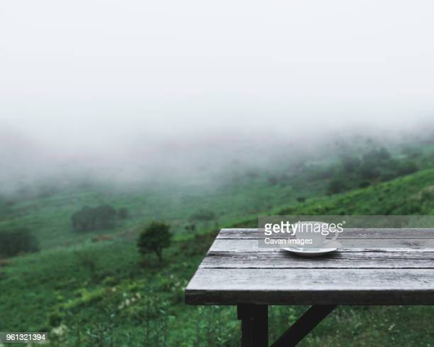 Coffee cup on table on mountain during foggy weather