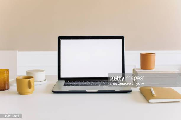 coffee cup on table - laptop mockup stock photos and pictures