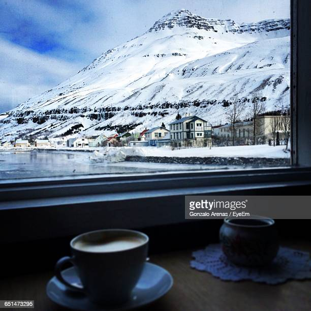 Coffee Cup On Table With Snowcapped Mountain Seen Through Glass Window
