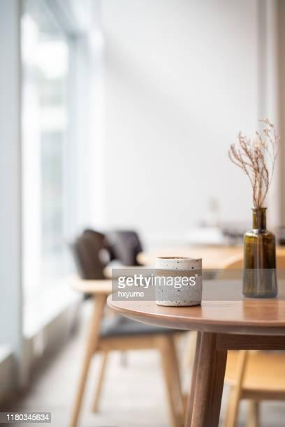 kaffeetasse auf holztisch neben fenster - couchtisch stock-fotos und bilder