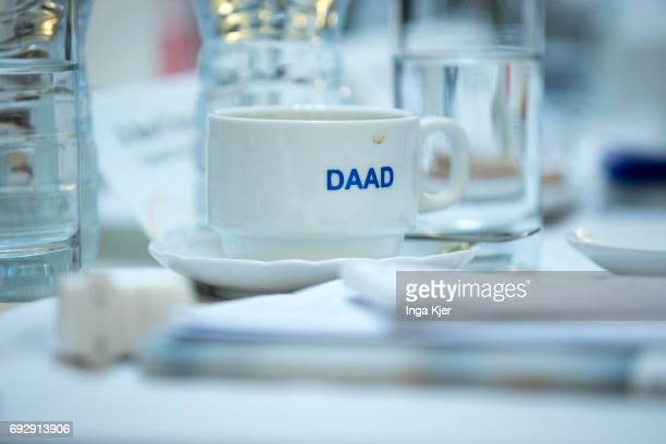 A coffee cup on which the logo of the German Academic Exchange Service is printed is on a table during the 'DAAD HighLevel Experts Dialogue' on April...