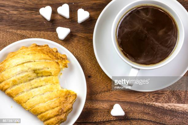 Coffee cup with apple danish pastry and Heart Shape Sugar Cubes. Sweet dessert
