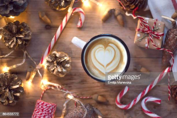 Coffee cup with Christmas ornaments and decoration on wooden background