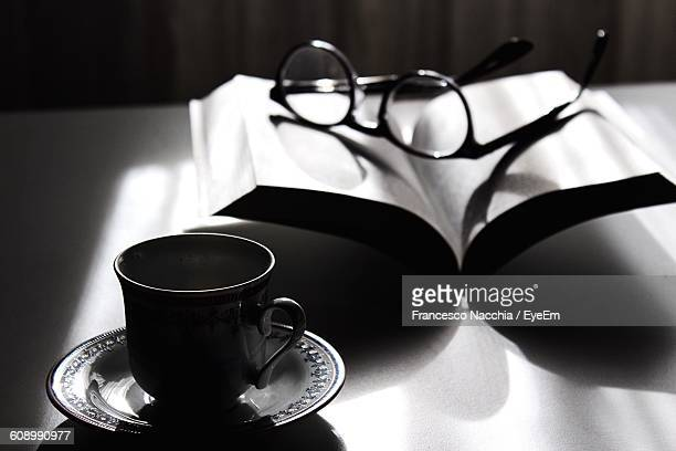 Coffee Cup With Eyeglasses On Open Book At Table