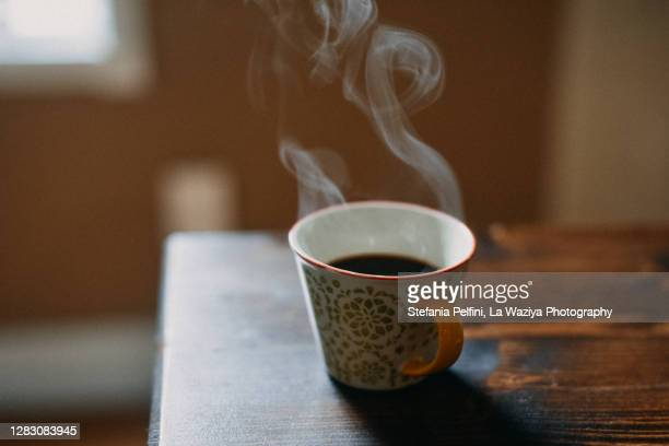 coffee cup with hot steam on wooden table. - steeping stock pictures, royalty-free photos & images
