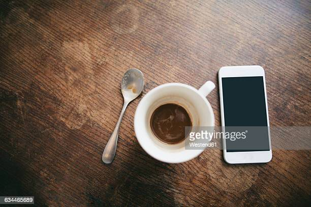 Coffee cup with remains of coffee, spoon and smartphone on wood