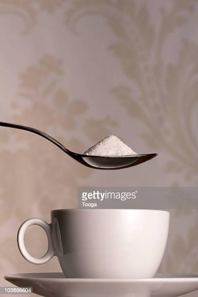 coffee cup with teaspoon of sugar