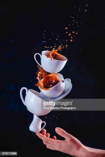 Coffee cups stack with a dynamic splash balancing on a tip of a finger. High-speed food photography in motion. Dark background with copy space
