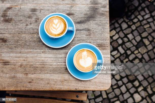 coffee cups with cappuccino latte art on the table directly above view - two objects stock photos and pictures
