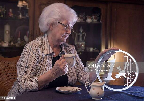 Coffee drinking pensioner with 1 Euro coin made of glass Symbol photo on the topics pension poverty poverty in old age twilight years etc on January...