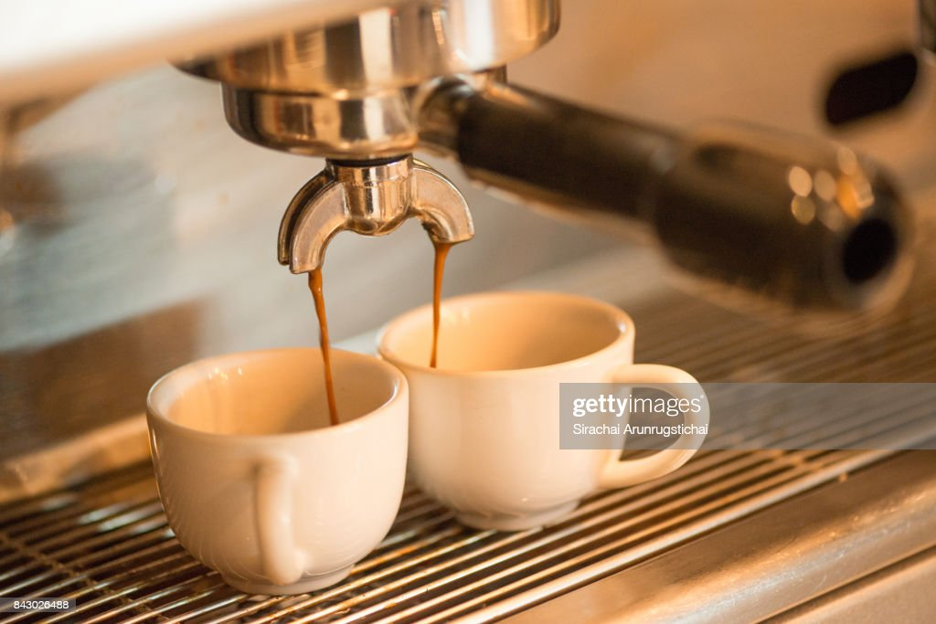 Coffee drips into two coffee cup from Espresso Machine : Stock Photo