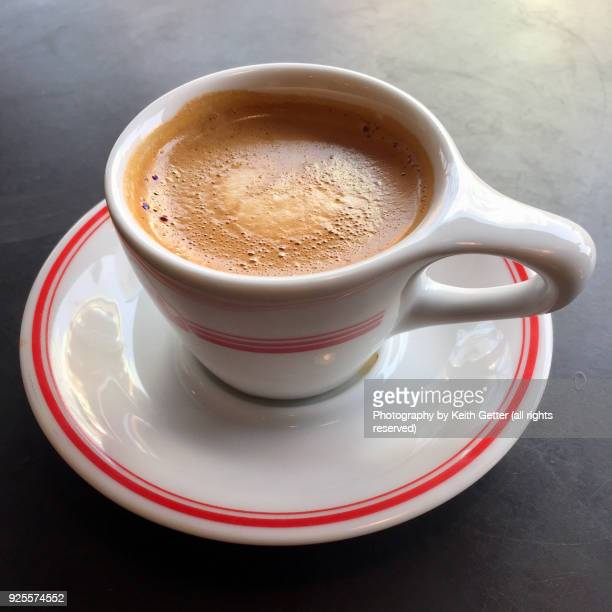 coffee espresso drink in a porcelain mug on a saucer resting on a black tabletop - coffee drink stock pictures, royalty-free photos & images