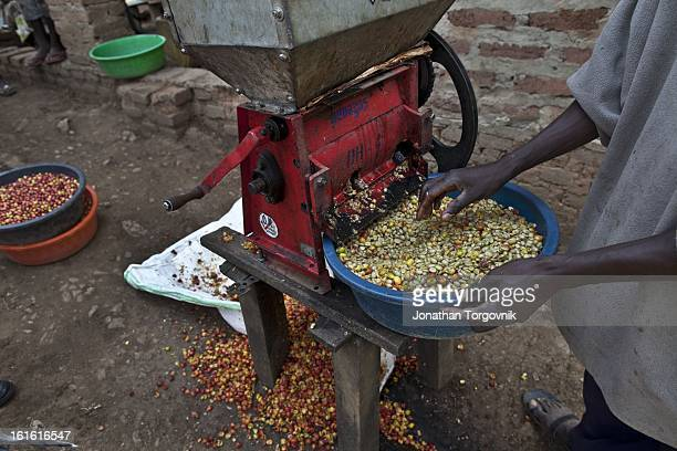 Coffee farmers use a hand cranked coffee cherry pulper machine on March 7 2012 in Kasese Uganda Andrew Rugasira Chairman and CEO of Good African...