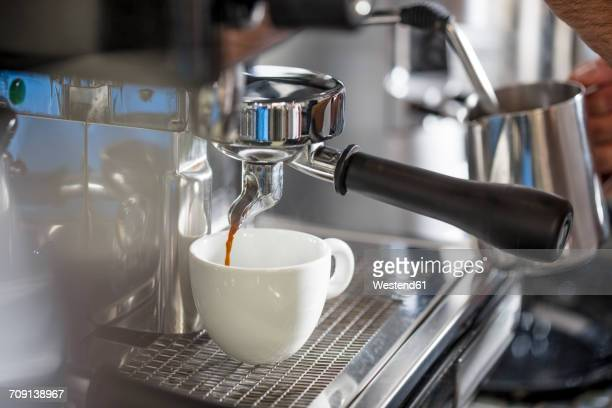 Coffee from espresso machine pouring into cup