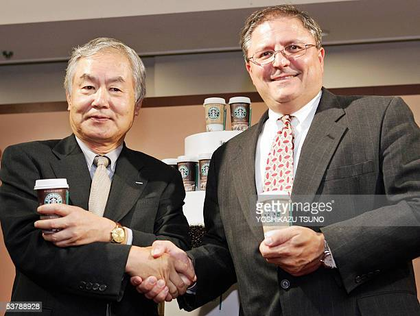 Coffee giant Starbucks senior vice president Gerardo Lopez shakes hands with Akinobu Kodaira, president of Japanese beverage giant Suntory in Tokyo,...