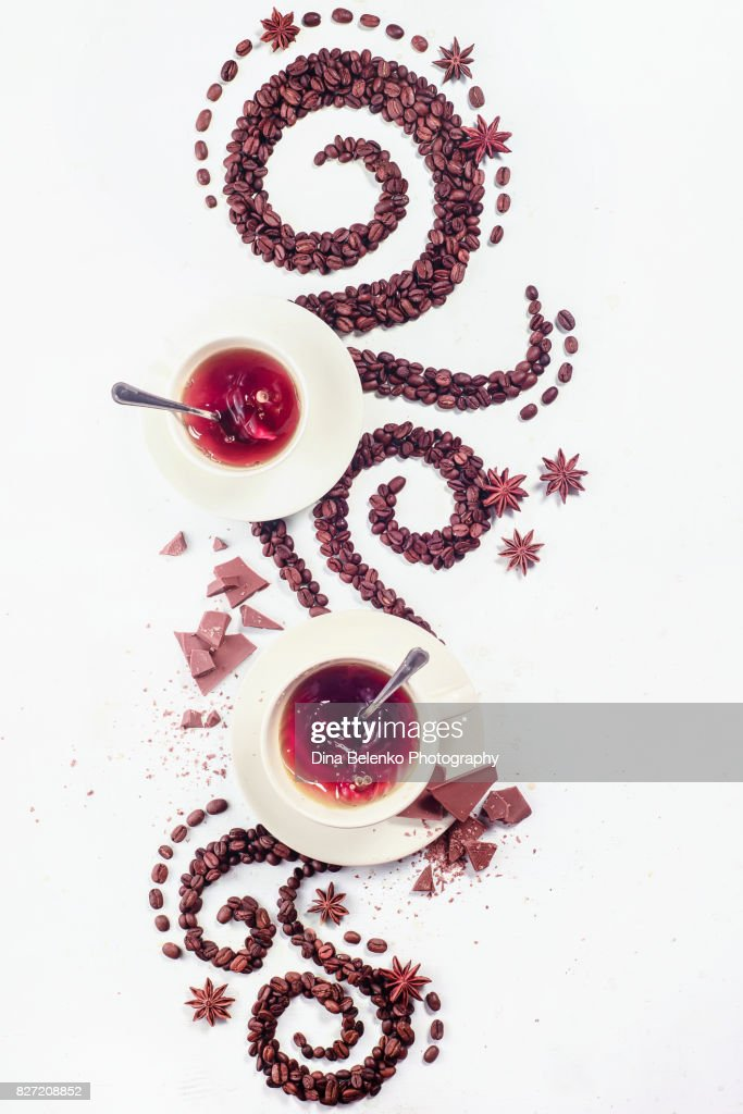 Coffee grains lying in the shape of a swirl with the cup, cinnamon, anise stars and chocolate : Stock Photo