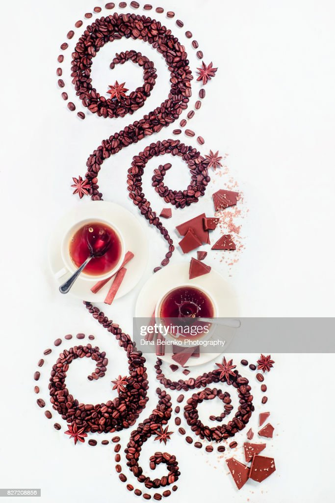 Coffee grains lying in the shape of a swirl with the cup, cinnamon, anise stars, chocolate : Stock Photo