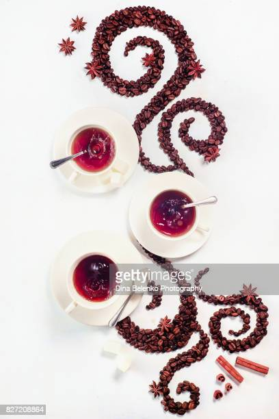 Coffee grains lying in the shape of a swirl with the cup, cinnamon, anise stars