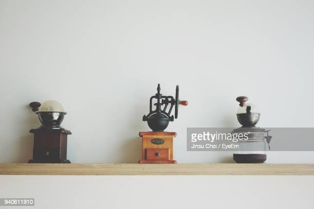 coffee grinders on table against wall - coffee grinder stock photos and pictures