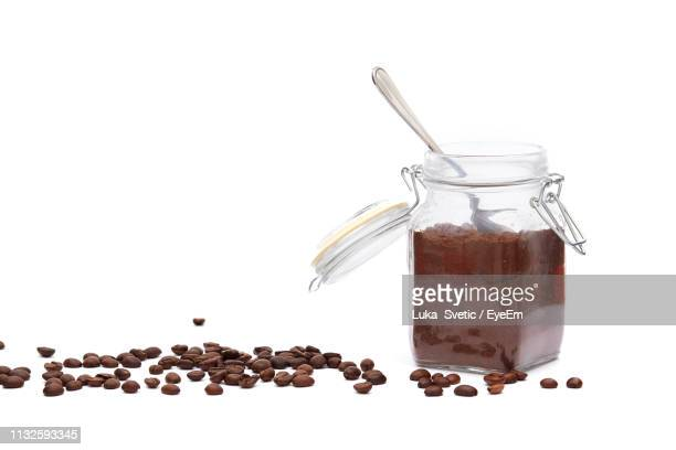 coffee ground with beans in jar against white background - ground coffee stock photos and pictures