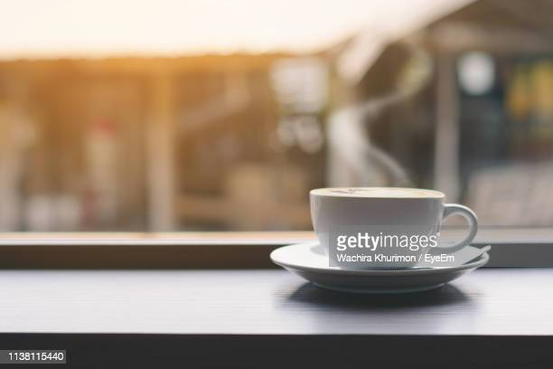 coffee in cup on window sill - window sill stock pictures, royalty-free photos & images