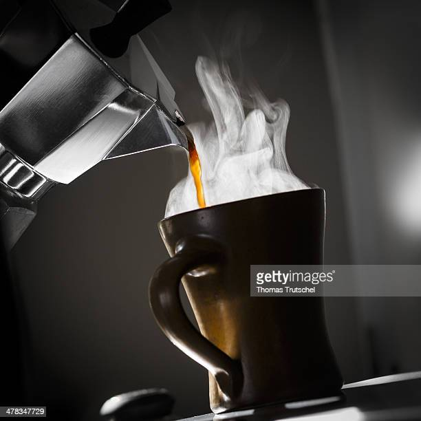 Coffee is being poured into a coffee cup in backlight on March 09 in Berlin Germany