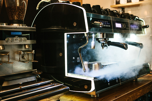 Coffee machine with steam in the process. A cafe 868051546