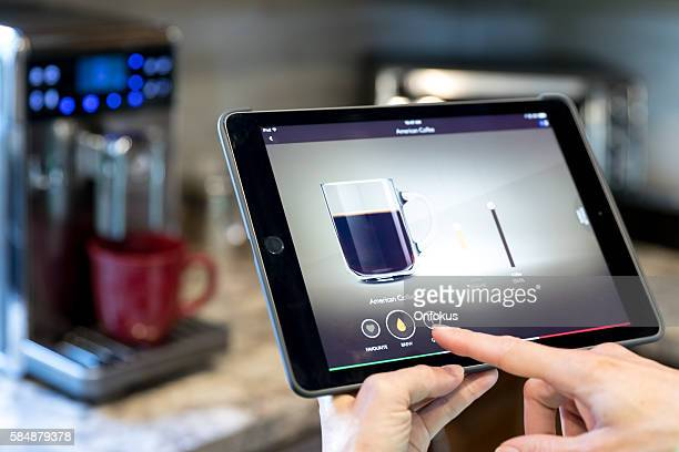 coffee maker inside smart homes being controlled on digital tablet - haushaltsmaschine stock-fotos und bilder