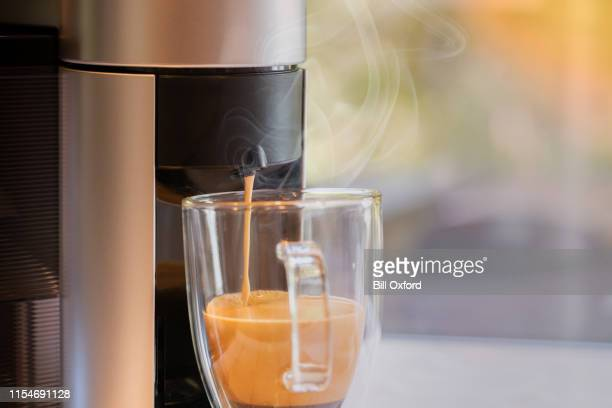 coffee maker pouring into glass mug - coffee maker stock pictures, royalty-free photos & images