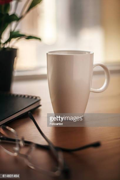 A coffee mug on a wooden table next to a window