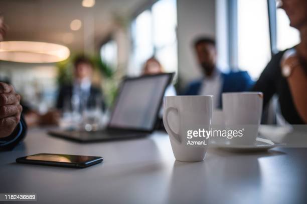coffee mugs and smart phone on conference table - tavolo da conferenza foto e immagini stock