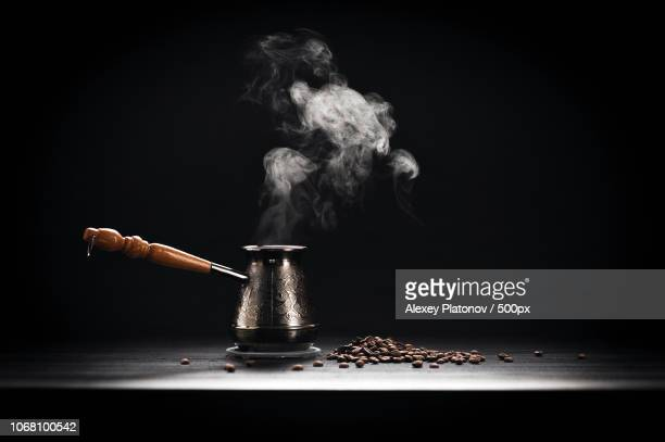 coffee pot and roasted coffee beans on black background - steam stock pictures, royalty-free photos & images
