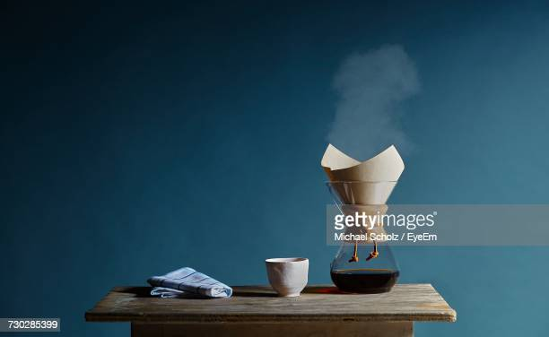 Coffee Pot With Cup And Napkin On Table Against Blue Wall