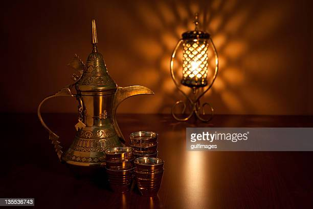 Coffee pot with cups and illuminated lantern