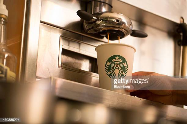 Coffee pours from a coffee machine into a cardboard coffee cup inside a Starbucks Corp coffee shop in London UK on Monday June 9 2014 UK services...