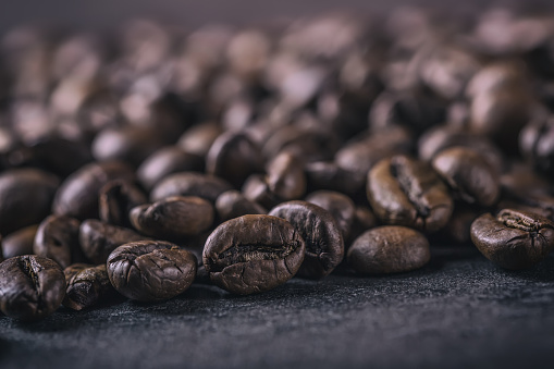 Coffee. Roasted coffee beans spilled freely on a concrete background 518499320