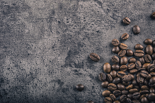 Coffee. Roasted coffee beans spilled freely on a concrete background 518500508