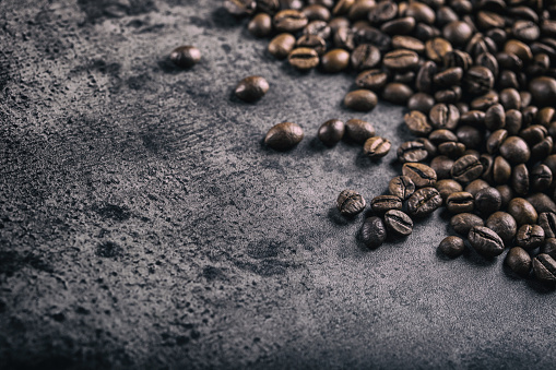 Coffee. Roasted coffee beans spilled freely on a concrete background 518501586