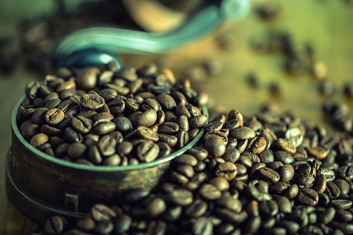 Coffee. Roasted coffee beans spilled freely on a wooden table. 487143662