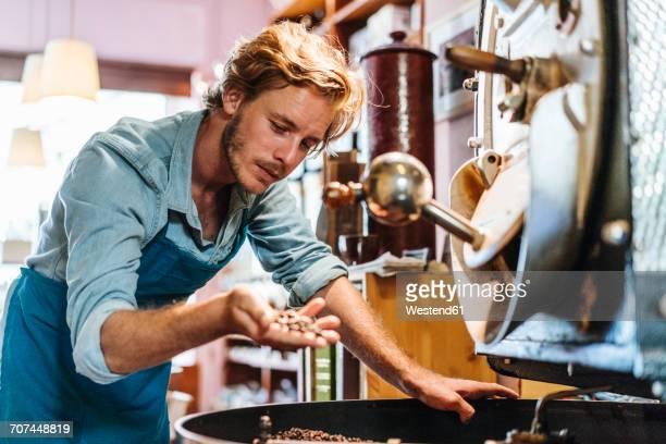 coffee roaster in his shop examining coffee beans - attività foto e immagini stock