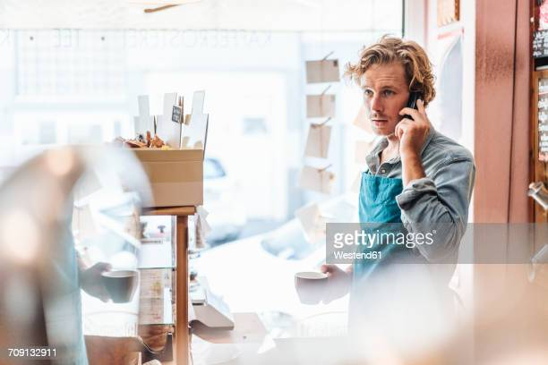 coffee roaster in his shop on the phone - assistant stock pictures, royalty-free photos & images
